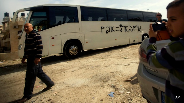 """A Palestinian boy takes a photo of graffiti with Hebrew that reads """"non-Jews in Israel equals enemies,"""" on a bus in an Arab neighborhood in Jerusalem, Monday, March 24, 2014. Israeli police say vandals have slashed car tires and sprayed a bus with hate graffiti in a predominantly Arab neighborhood in Jerusalem. (AP Photo/Sebastian Scheiner)"""